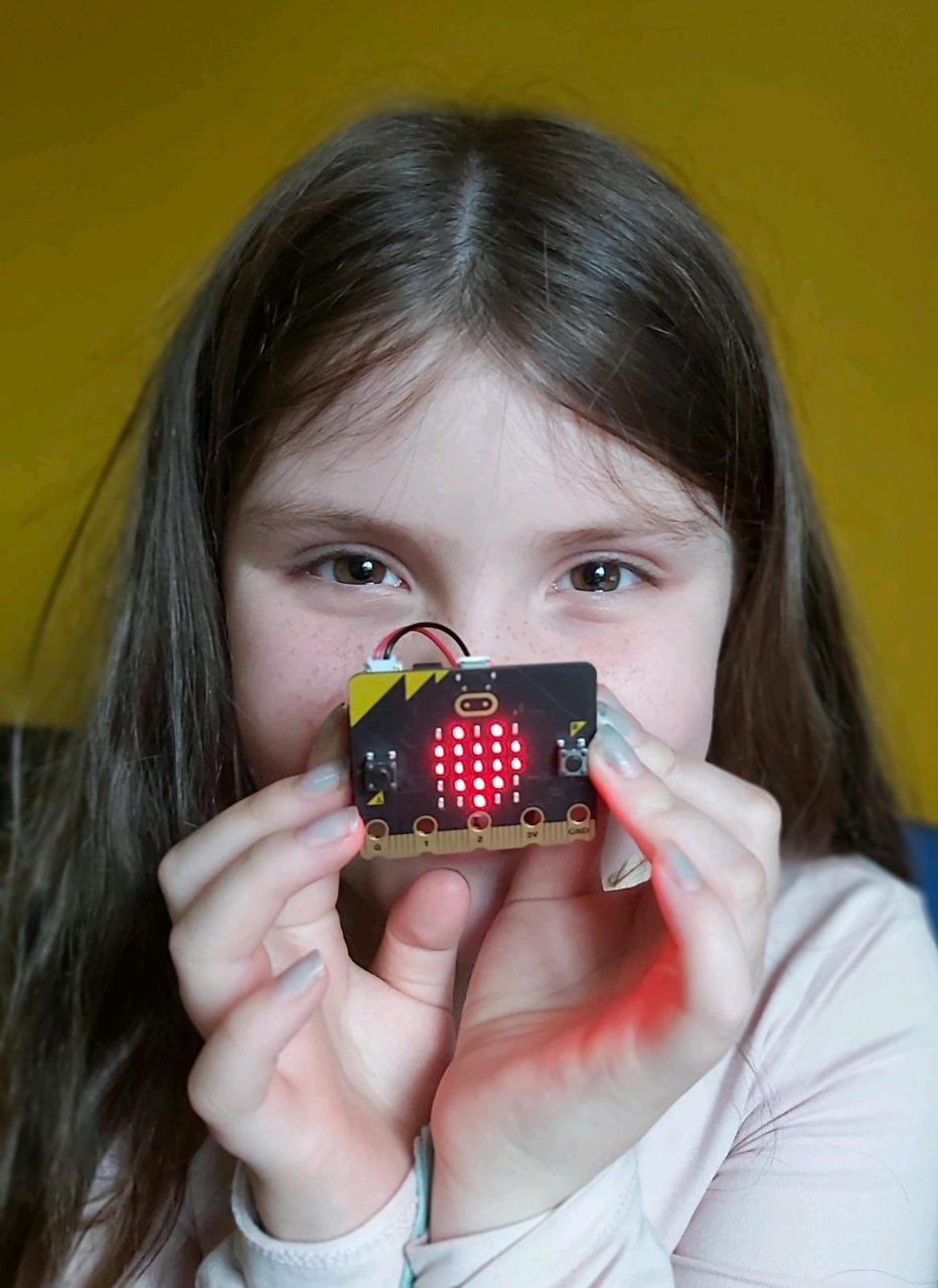 student holding microbit