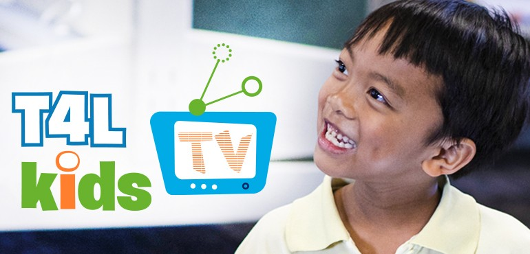 Student smiling in front of T4L TV logo